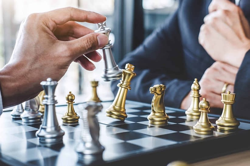 Two businessman playing chess game to plan strategy for success,