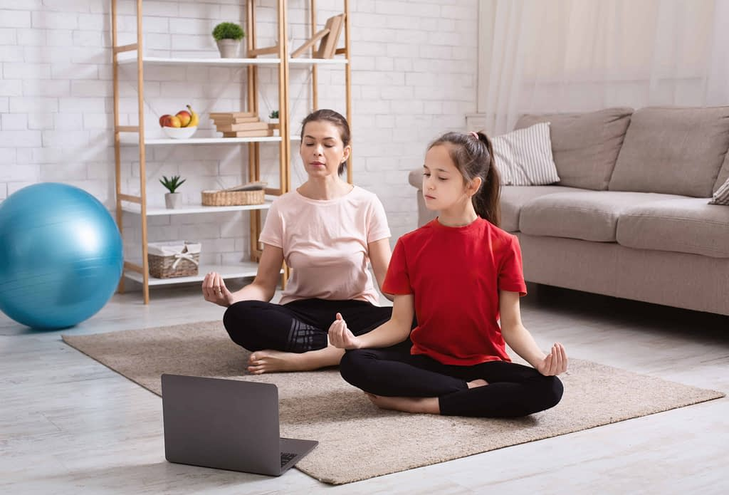 Home yoga workout. Mom and teen daughter meditating to online tutorial on laptop in living room